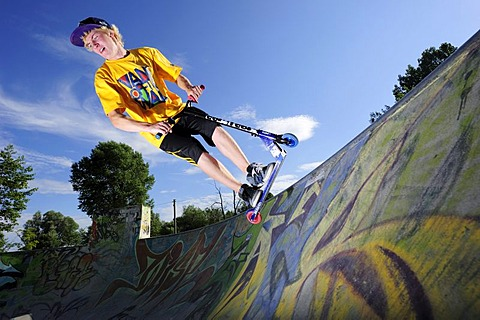 Young man performing jump with scooter, skate park, Munich, Upper Bavaria, Germany